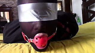 Laura XXX is wearing panthyhose and high heels. She's hogtied, masked, blindfolded and ballgagged